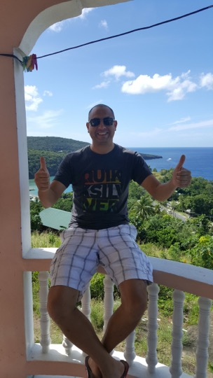 Steve Clarke wearing a t-shirt, giving thumbs up on a balcony overlooking the Caribbean